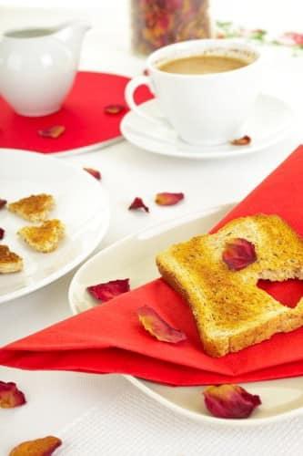 Красные салфетки и розовые лепестки для украшения стола на 14 февраля