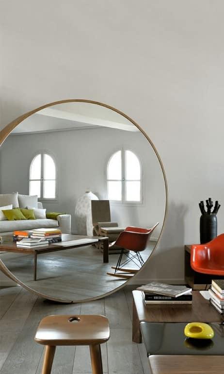 Большое круглое зеркало на полу гостиной фото