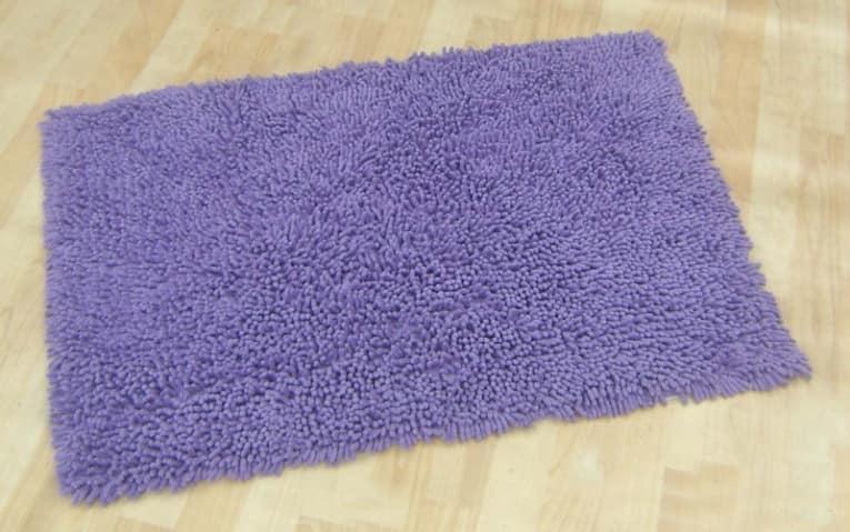 Фиолетовый ковер притягивает взгляд, и никто не заметит дефекты отделки стены