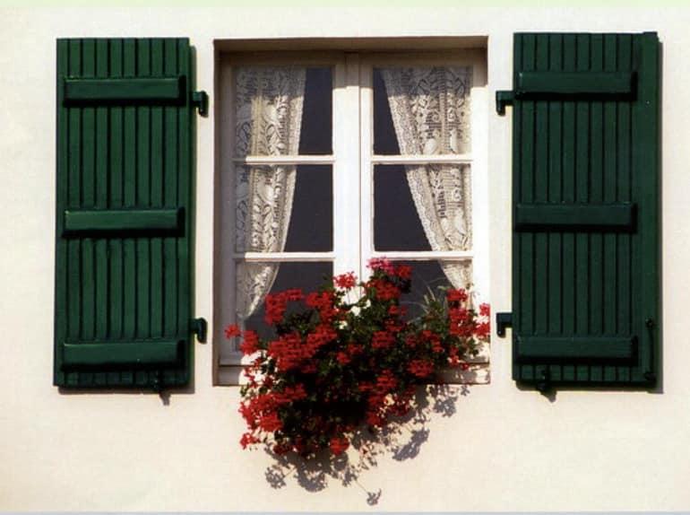 Зеленые ставни в сочетании с цветами на окнах