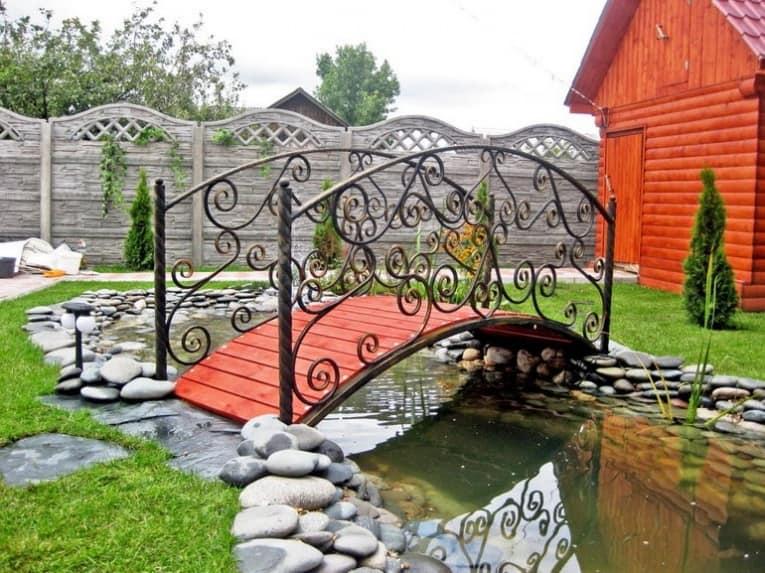 Красивый красный садовый мостик из маталла и дерева