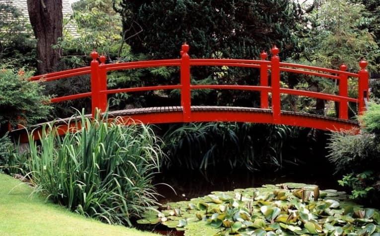 Яркий красный садовый мостик из дерева фото