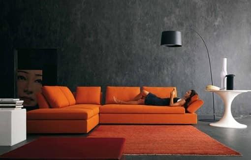 Яркий оранжевый диван и темные стены