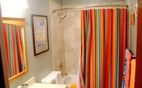Яркая шторка в ванной отвлечет внимание от пола