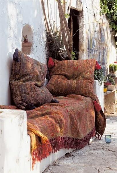 Каменная скамейка у стены дома