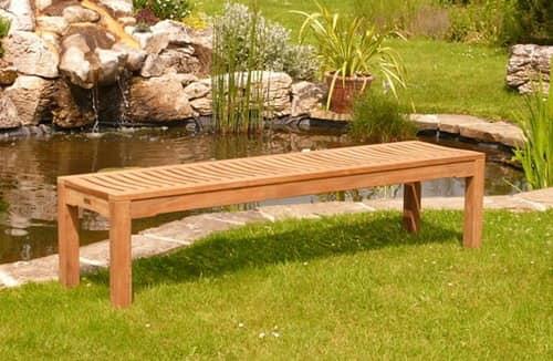 Деревяная скамейка без спинки у пруда
