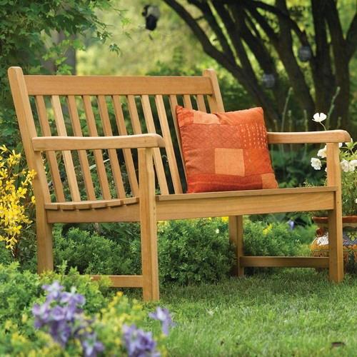 Уголок для отдыха в саду с деревянной скамейкой