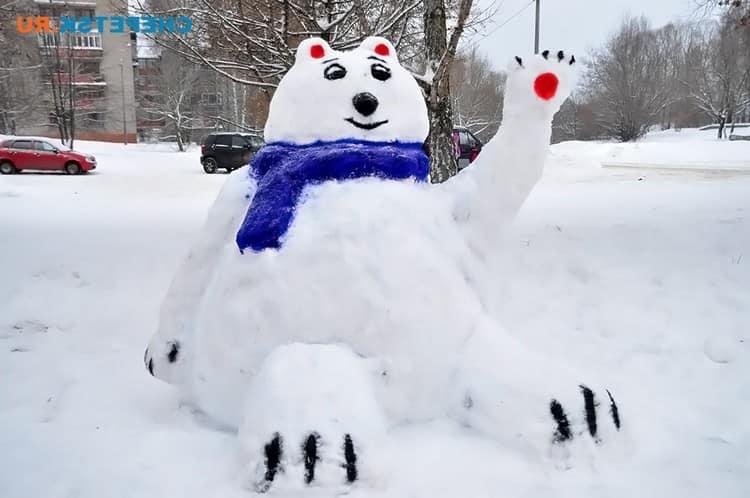 Медведь с поднятой лапой из снега
