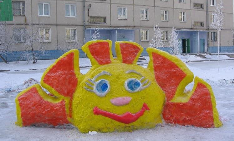 Позитивное солнышко, сделанное из снега и раскрашенное красками