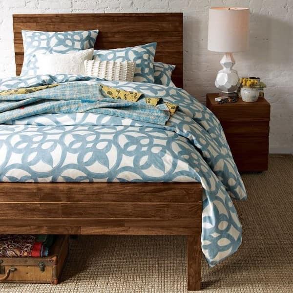 Темная кровать в светлой спальне