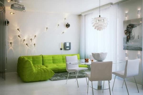 Зеленый диван - единственная яркая деталь белой гостиной