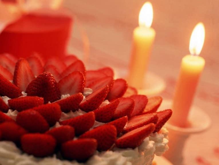Свечи на праздничном столе и клубника со сливками на десерт