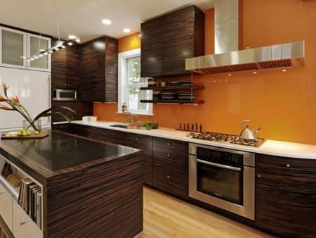 Оранжевые обои и коричневая мебель на кухне