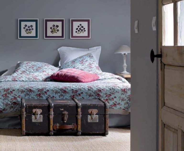 Старый чемодан и гербарии в интерьере спальни напоминают о приятном путешествии