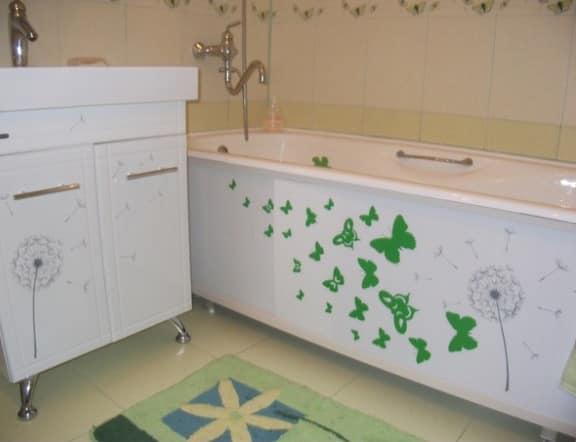 Зеленый коврик и рисунки на экране ванны оживляют однотонное белое помещение