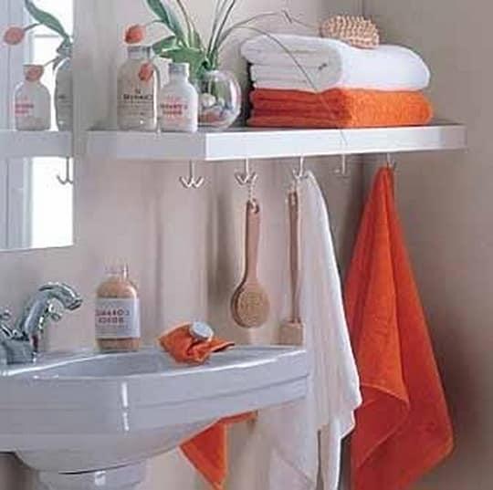 Интерьер однотонного санузла дополнен полками для разноцветных полотенец и зеркалом в красной раме