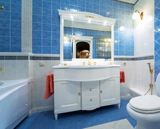 Яркие полотенца делают холодный бело-голубой интерьер ванной комнаты более уютным