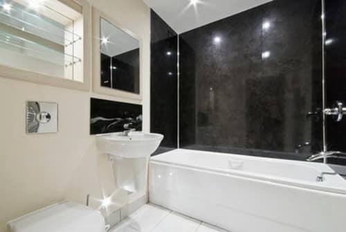 Яркое освещение украшает интерьер черно белой ванной