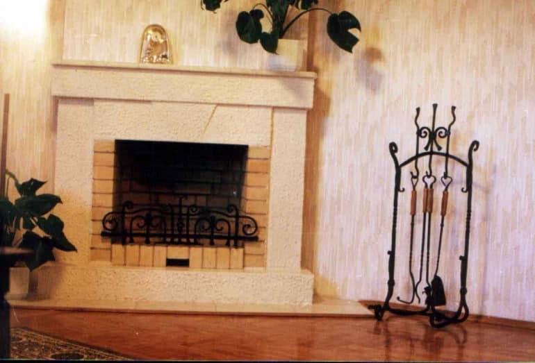 Кованая каминная решетка и набор для камина в интерьере гостиной