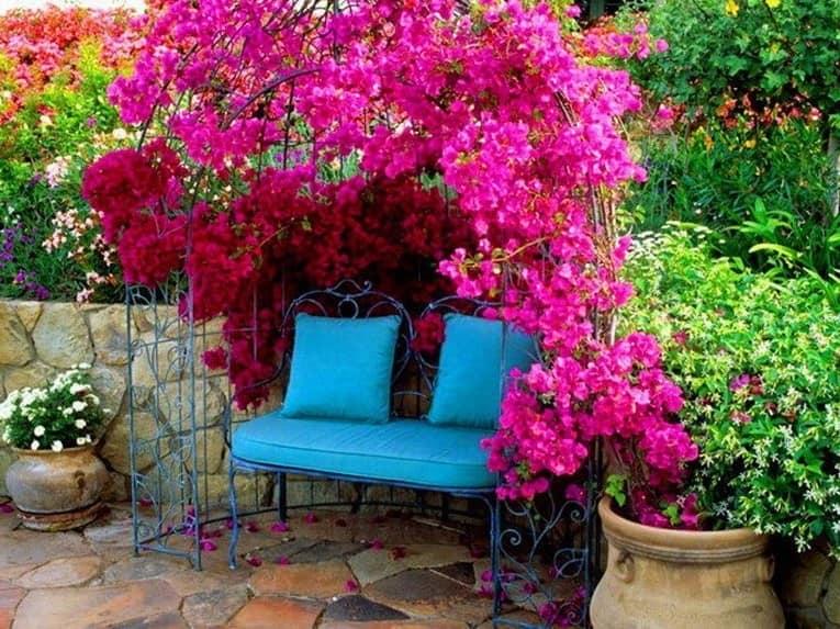 Металлическая арка с цветами в уголке отдыха в саду