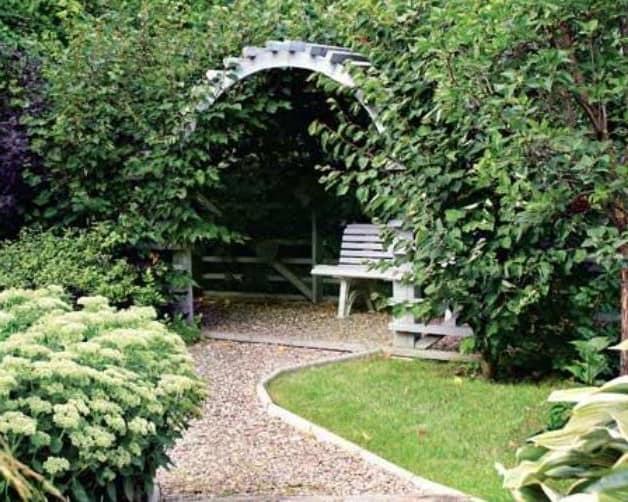Белая деревянная арка в саду и зеленые вьющиеся растения - уголок отдыха