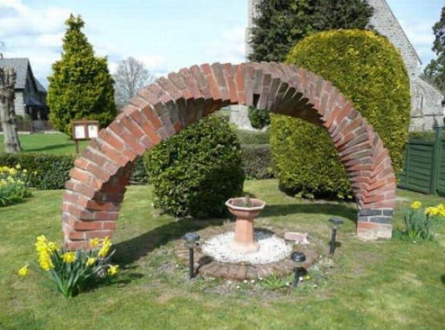 Витая кирпичная арка вместе садовой статуи