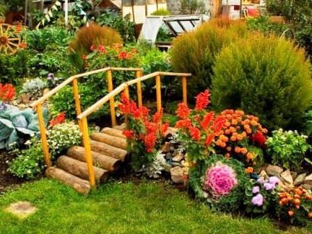 Кантри стиль сада: деревянный мостик и декоративный пруд или клумбы с цветами