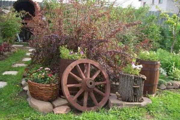 Атрибуты стиля кантри: колесо телеги, пеньки, корзинки, глиняные кувшины