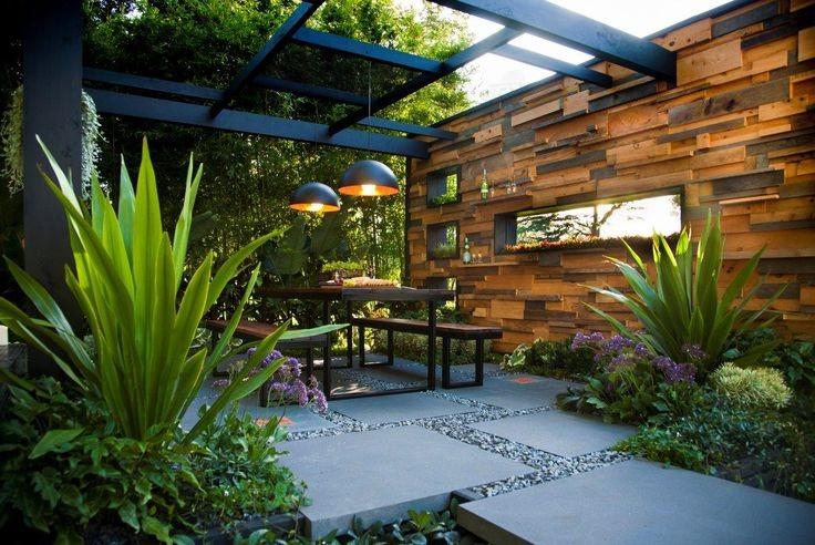 Прозрачный стеклянный навес от дождя в уголке отдыха в саду фото