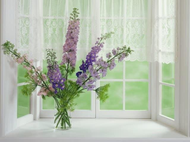 Ваза с цветами: яркий акцент на белом подоконнике