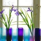 Разноцветные вазы на подоконнике