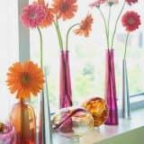 Яркие бутылки и вазы на окне