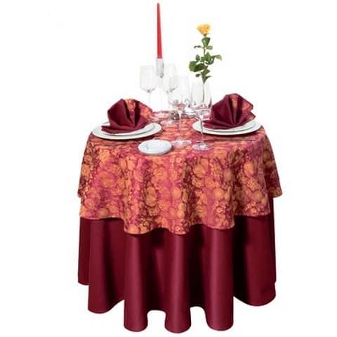 Красивое сочетание двух разных по цвету и фактуре скатертей на круглом столе