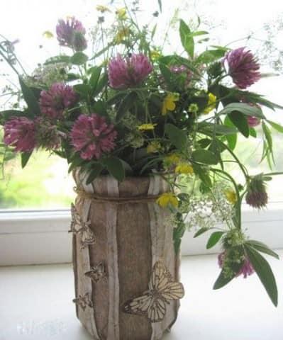 Такой оригинальный декор банки, выступающей в роли вазона, подчеркнет красоту цветов