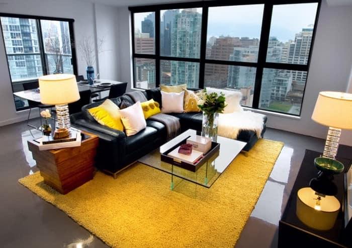 Сочетание черного дивана с ярким желтым ковром