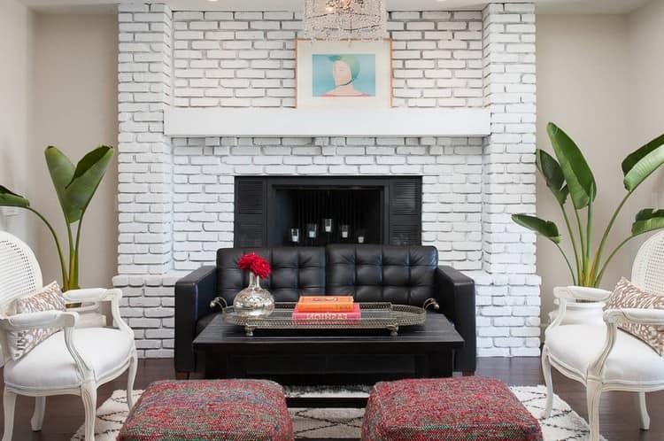 Белая кирпичная стена и черный диван в интерьере