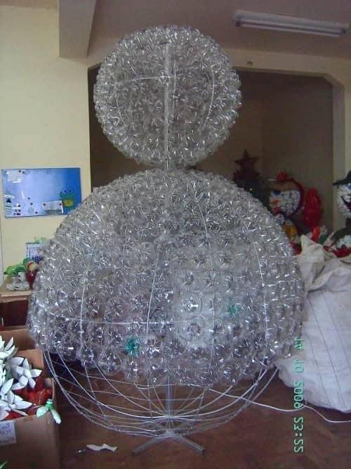 Вставляем бутылки в проволочный каркас, чтобы сделать большого снеговика