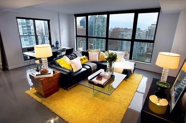 Яркий желтый ковер и несколько аксессуаров в серой гостиной + черный цвет