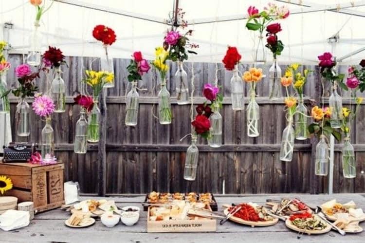 Уличный дачный декор из подвешенных стеклянных бутылок и цветов